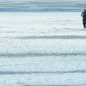 הכפר הוא מטאפורה. דייג צועד על אגם קפוא סמוך לעיר לאהטי שבפינלנד