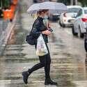אישה מחזיקה במטריה בזמן שגשם יורד בתל אביב, אתמול // צילום: יהושע יוסף