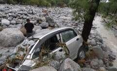 הודי מביט ברכב שניזוק בשל הגשמים והשיטפונות שהיכו את המדינה // צילום: אי.פי.אי