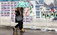 צעירים איראניים חולפים על פני תעמולת בחירות בטהרן // צילום: איי.פי