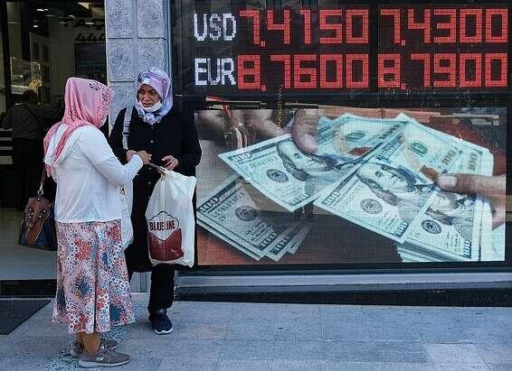 Femmes turques à côté d'une banque turque affichant les taux de change en rouge // Photo: Reuter